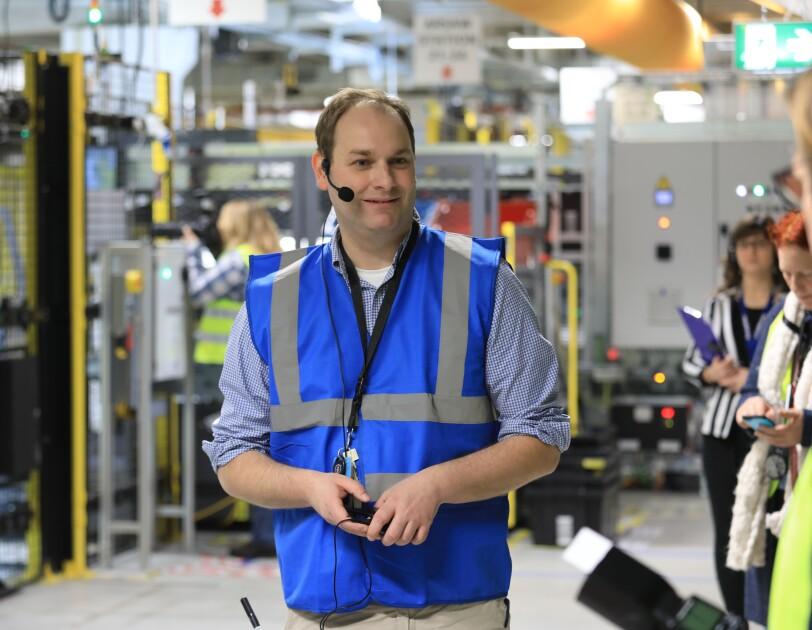 Ein Mann mit blauer Sicherheitsweste steht in einer Logistikhalle, hinter ihm sieht man Besucher