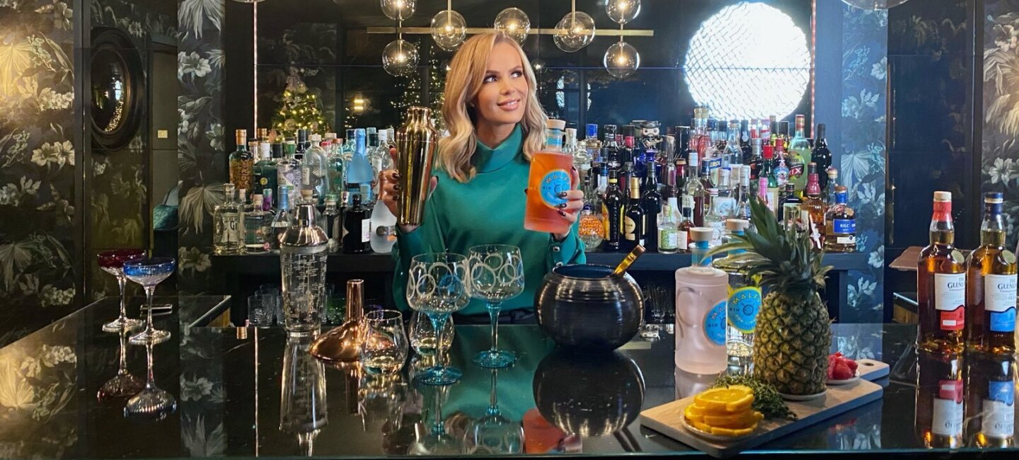 Amanda Holden holdng cocktail shaker sat at a bar surrounded by glass lighting