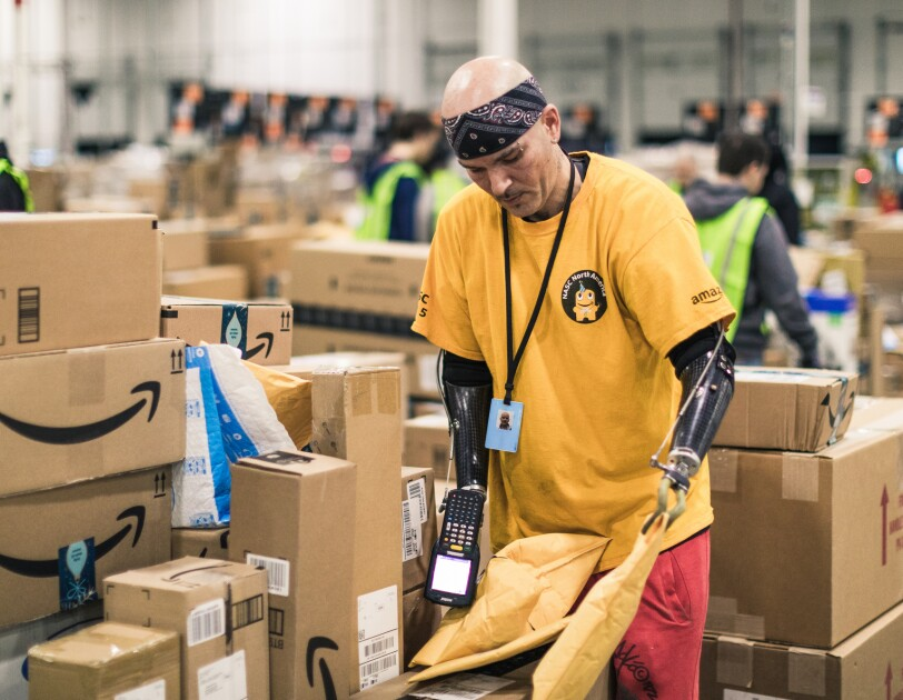 A man with dual arm prosthetics works in a large warehouse space surrounded by Amazon packages.