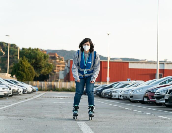 Silvia Mercado es asociada en el centro logístico de Amazon en Martorelles. Silvia está en el aparcamiento del centro logístico donde trabaja patinando. Silvia lleva el pelo  negro por el hombro y escalonado. Su jerseiy es de color gris y lleva un chaleco de Amazon Box Star de color azul y unos jeans. Lleva mascarilla de color blanco.