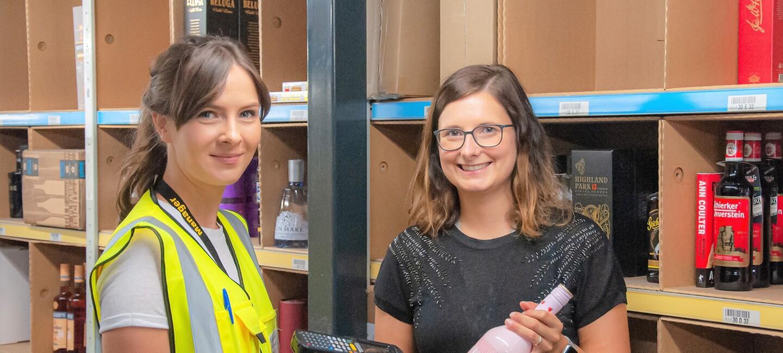 Isabelle steht links neben Larissa, im Hintergrund Regale mit Wein und Spirituosen. Isabelle hält einen Scanner in der Hand, Larissa eine Likörflasche.