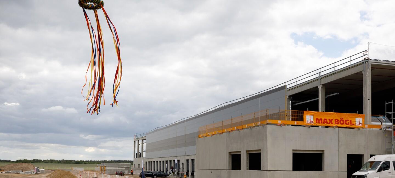 Ein Rohbau auf einer Baustelle, im Bild sieht man einen Richtkranz