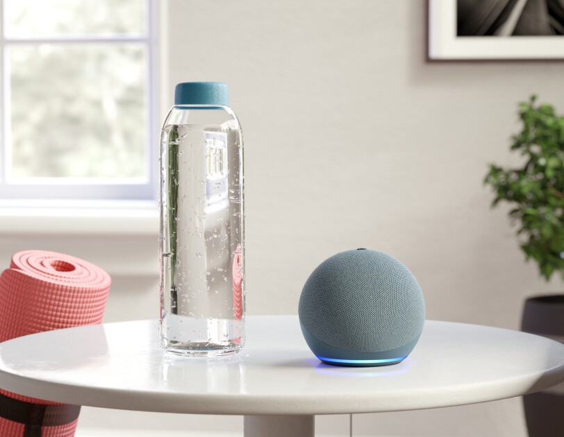 An Amazon Echo dot on a small table next to a bottle of water, leaning on the table is a pink yoga mat.