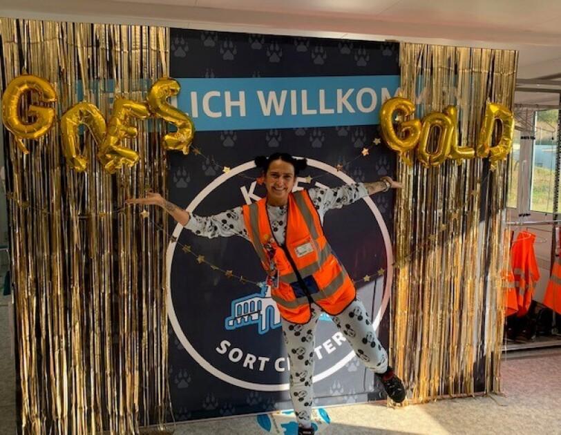 """Eine Mitarbeiterin steht im Schlafanzug im Sortierzentrum in Wolfhagen vor einem Bild auf dem """"Amazon goes gold"""" steht."""
