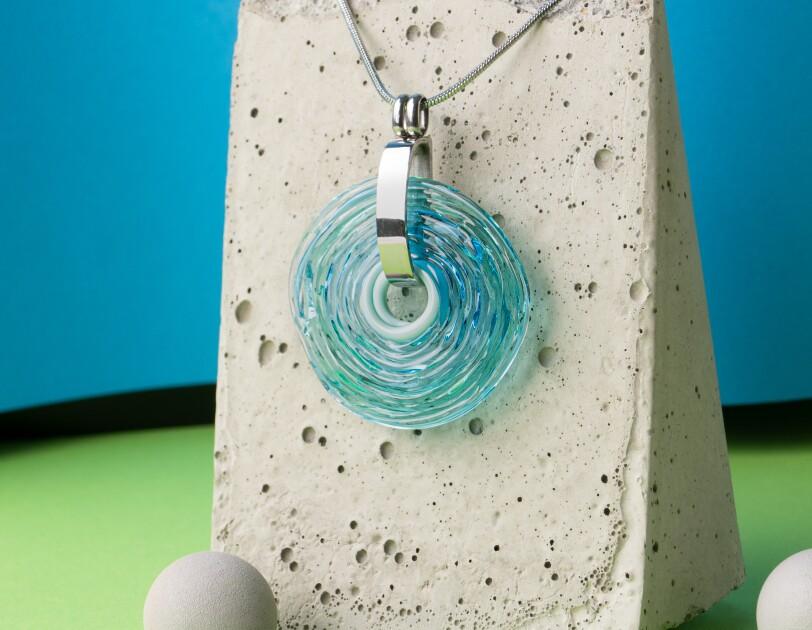 Über einem Steinbehälter hängt ein Kettenanhänger in blauem Glas.