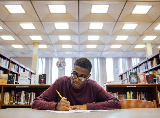 This Amazon Future Engineer image shows a teen studying in a library environment.