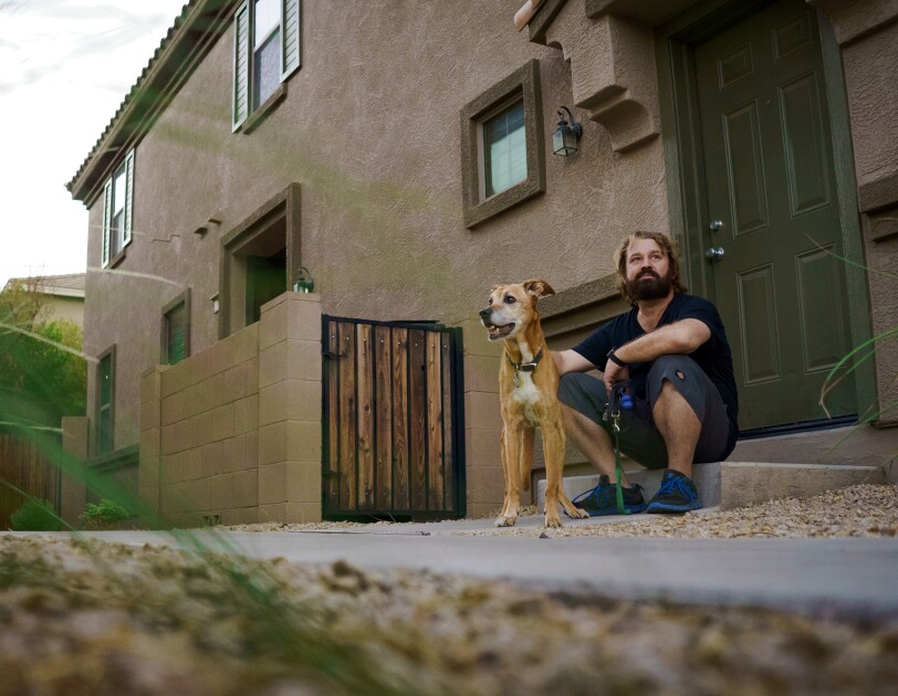 A dog and a man sitting on the doorstep of a home.