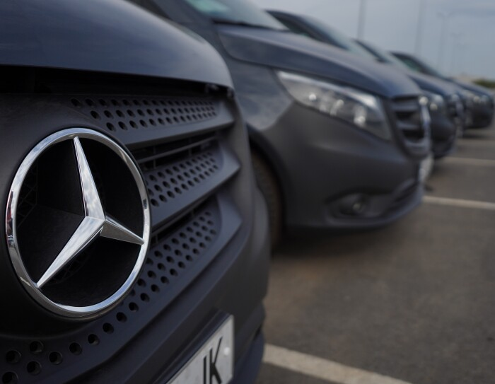 Una Mercedes Benz-Vans en un aparcamiento en primer plano. Detrás s even tres furgonetas más. En el primer plano se ve el logo de Mercedes-Benz.