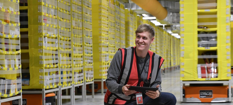Ein Amazon Mitarbeiter im Logistikzentrum in Winsen HAM2 gemeinsam mit einem Roboter.