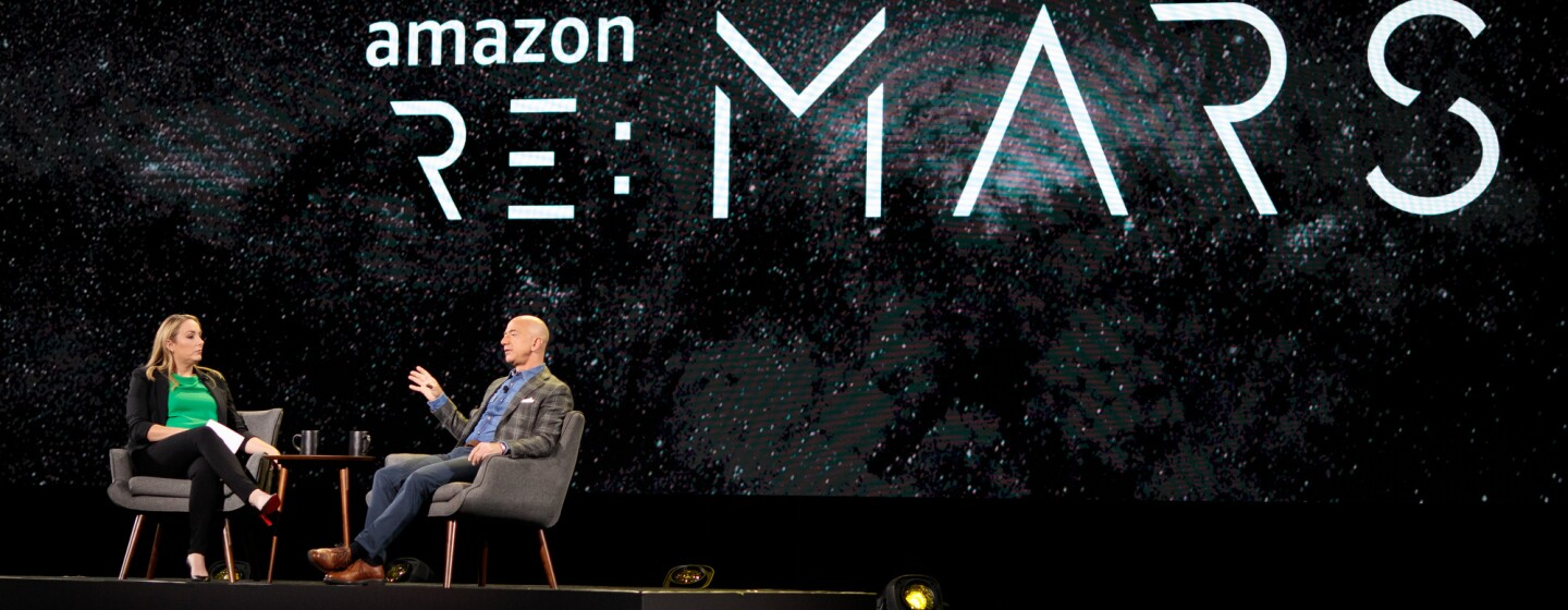 Jeff Bezos and Jenny Freshwater sit in chairs on stage at re:MARS 2019, for a fireside chat.