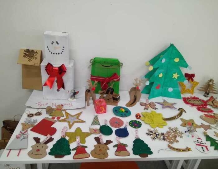 Adorno Navideño de MAD4. En una mesa de color blanco está lleno de decoraciones para colgar en el árbol: renos, árboles, camoanas, papá noel, estrella fugaz, estrellas.