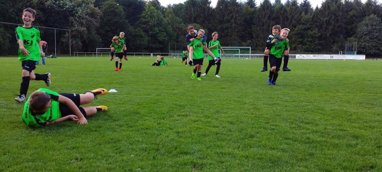 Eine Jungen-Fußballmannschaft spielt in grünen Tikots aus dem Rasen. Einige Jungen tragen ihre Freunde Huckepack, andere rennen oder sitzen auf dem Gras. Alle Kinder lachen und haben Spaß.