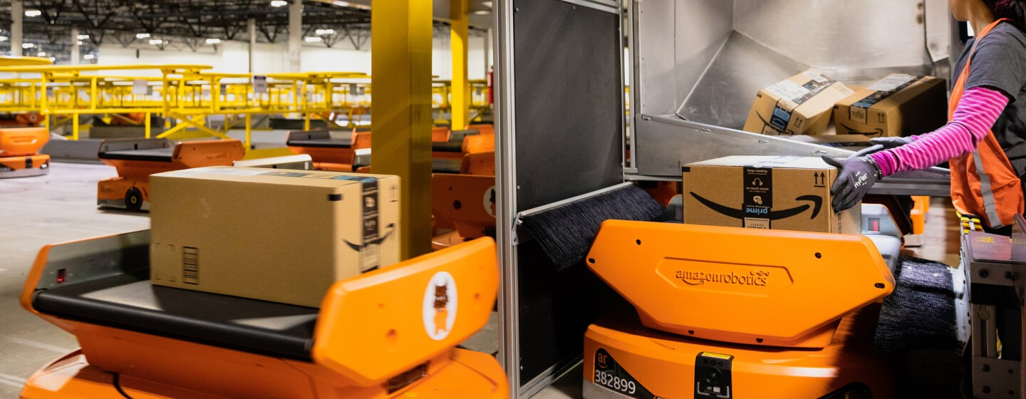 A worker touches a cardboard box that sits on top of one of several orange robotic units in the image.