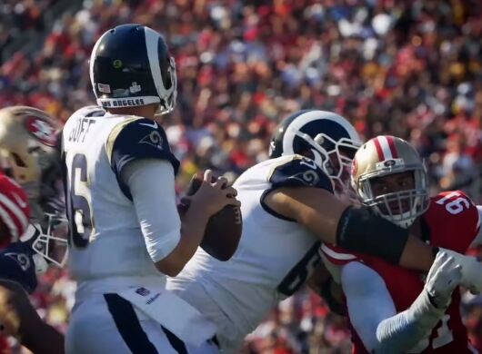 NFL Rams take on San Francisco. One man holds the ball as he readies to throw it. A teammate tackles an opponent, while another oppontent rushes the man holding the ball.