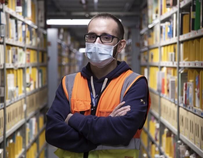Uomo ripreso a mezzo busto all'interno di un corridoio di scaffali in un magazzino Amazon. L'uomo indossa degli occhiali da vista e una mascherina chirurgica sul volto. Indossa anche un giubbino catarinfrangente e una felpa blu.