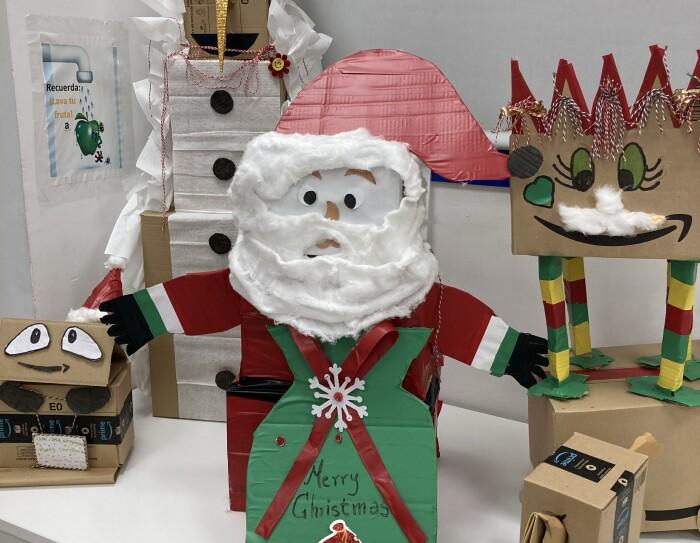 Adorno navideño de DMA1. Encima de una mesa de color blanco hay diferentes decoraciones navideñas hechas con cajas de cartón: un papá Noel, un elfo y un muñeco de nueve.