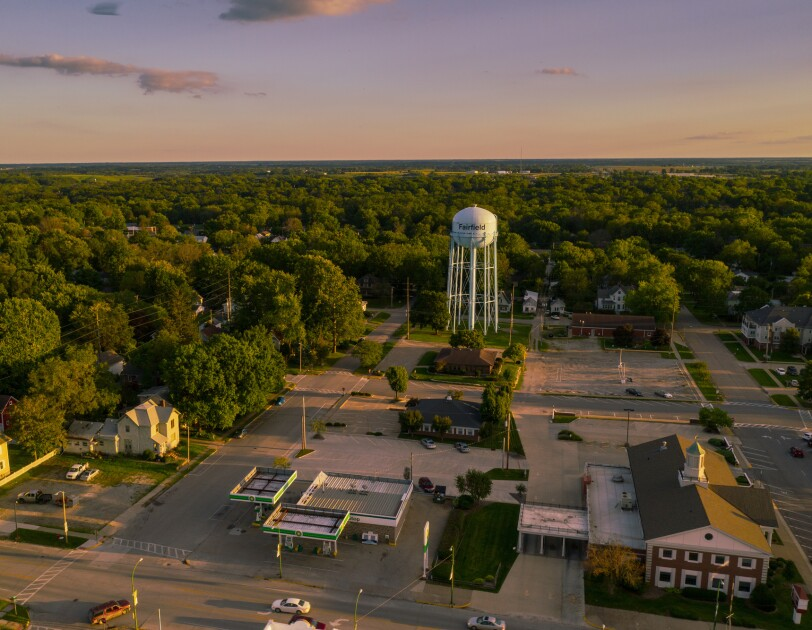 Aerial shot of a small town. A water tower stands near a wooded area that stretches to the horizon.