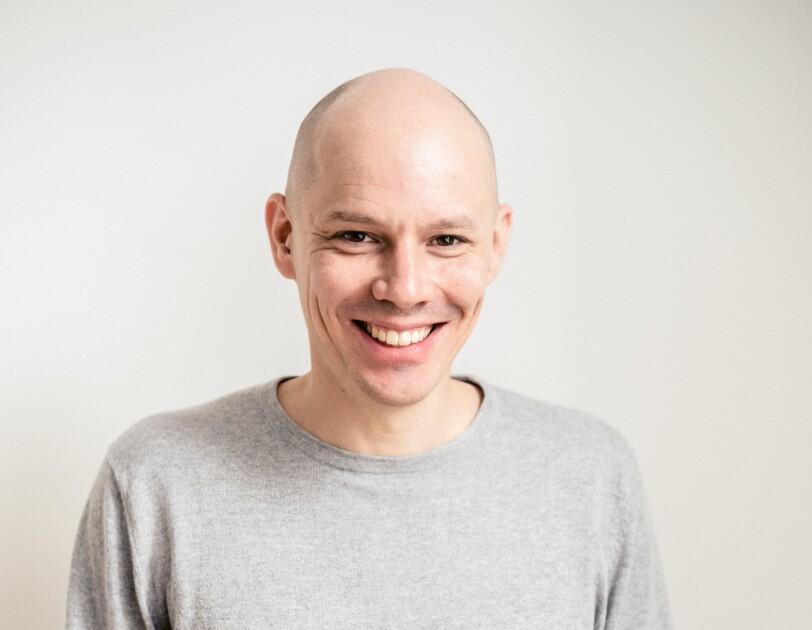 Ein Mann in einem hellgrauen Pullover schaut lachend in die Kamera. Er hat eine Glatze und braune Augen.