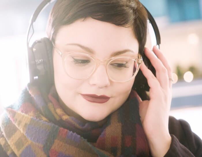 Ritratto di Giulia Massari, Marketing Manager Audible, mentre indossa delle cuffie e ascolta della musica.