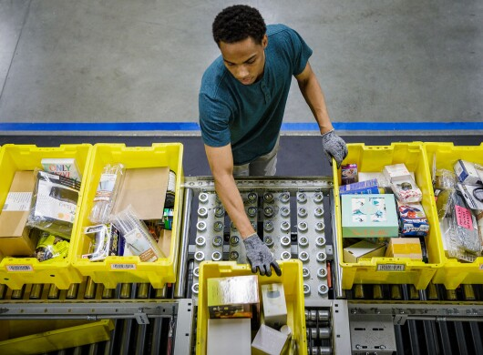 An Amazon Fulfillment center employee pulls a packing crate onto a conveyor belt full of packing crates.