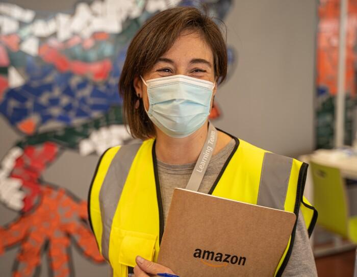 Marta Casasayas, responsable del programa de Aprendizaje de Amazon en España. De fondo una pare de colores. Marta sonriente y con mascarilla mira a c´ámara, sujeranto con la mano izquierda una carpeta de Amazon. Tiene media melena castaña pero de un lado es más corta que del otro.