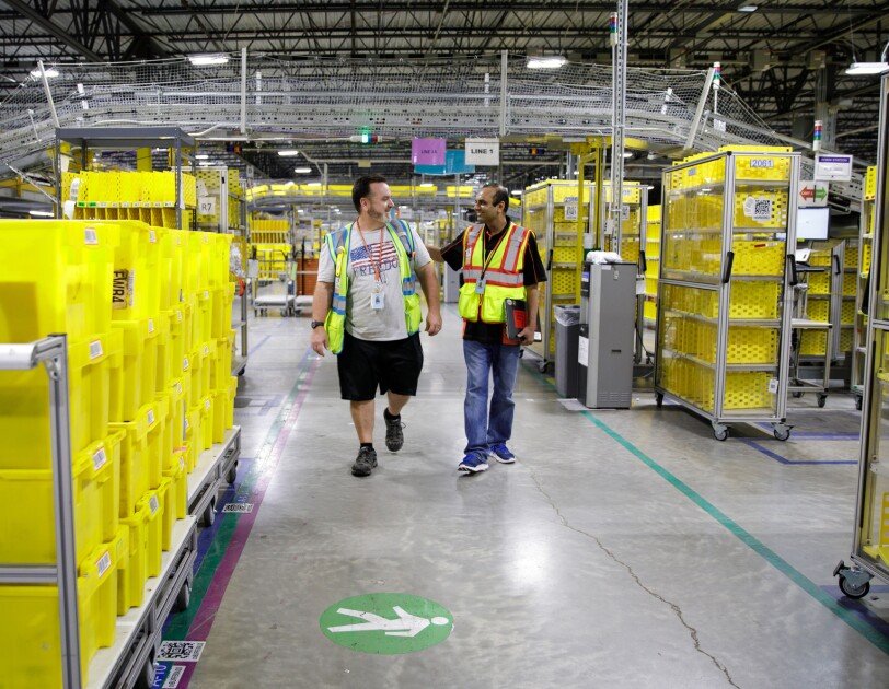 Two men walk along an aisle in a large warehouse space.