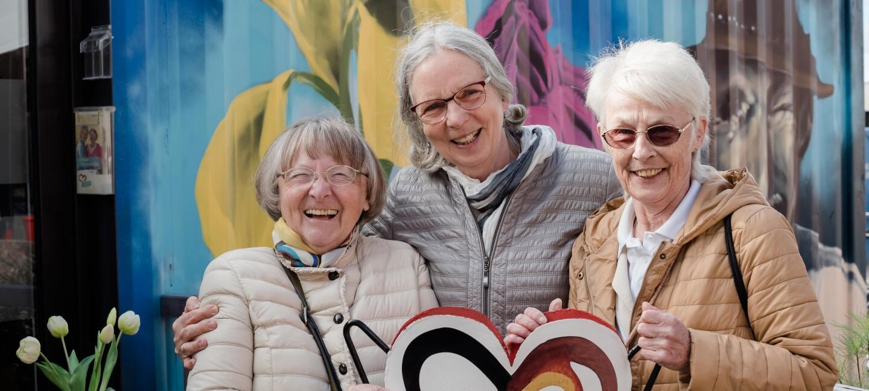 Drei ältere Damen lächeln in die Kamera.