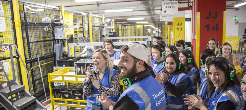 Foto di gruppo di visitatori di un magazzino Amazon durante un tour