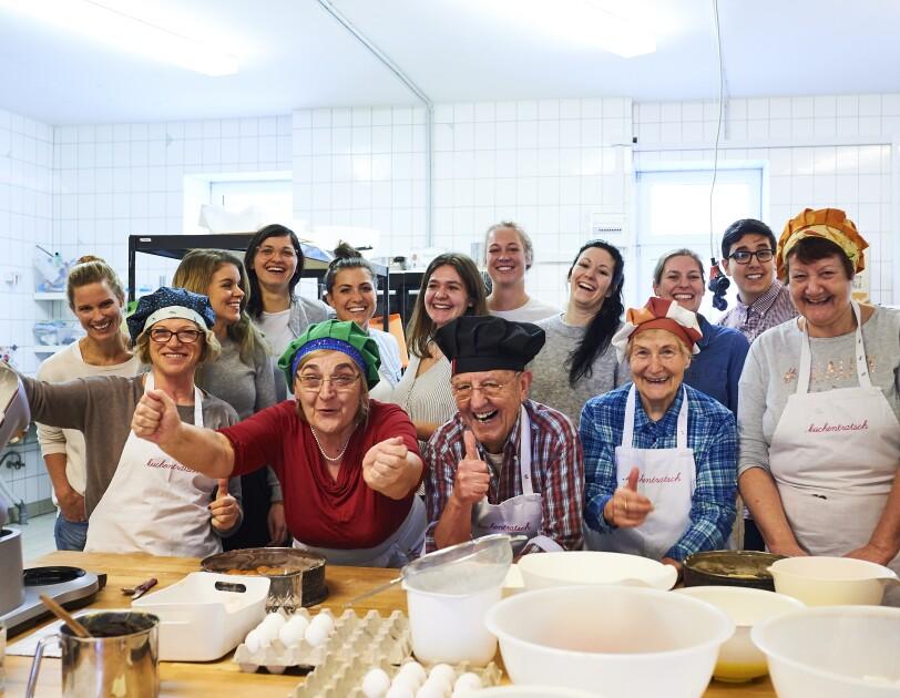 Das Team von Kuchentratsch steht in der Backstube und lacht in die Kamera. Sie tragen Schürzen und Kochmützen.