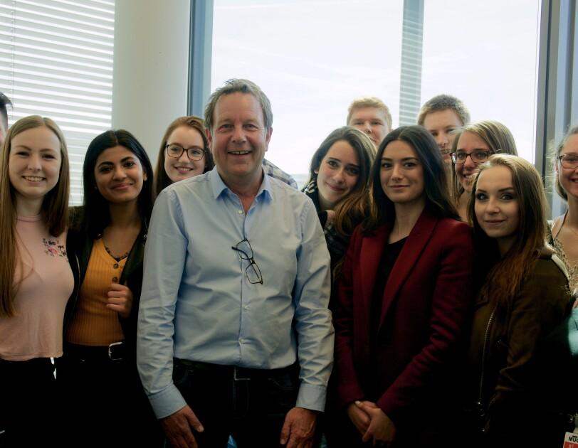 Eine Gruppe von Schülern posiert mit Ralf Kleber fürs Foto.