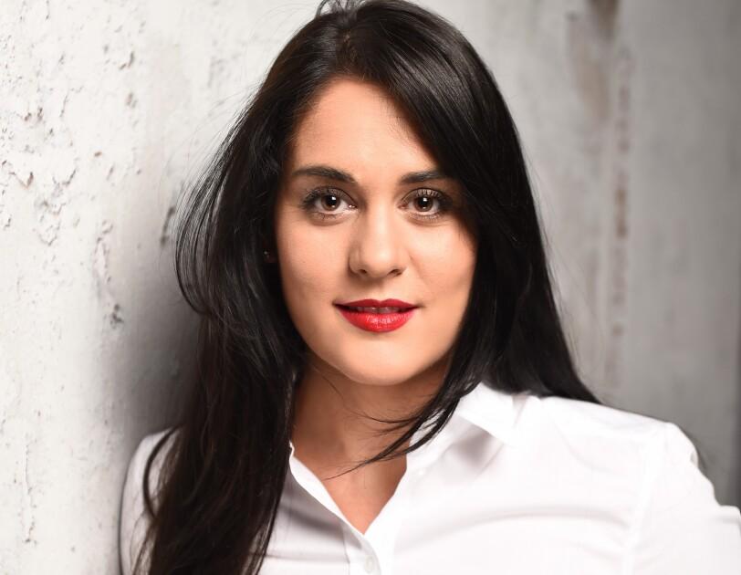 Eine Frau mit schwarzen Haaren und einer weißen Bluse lächelt in die Kamera.