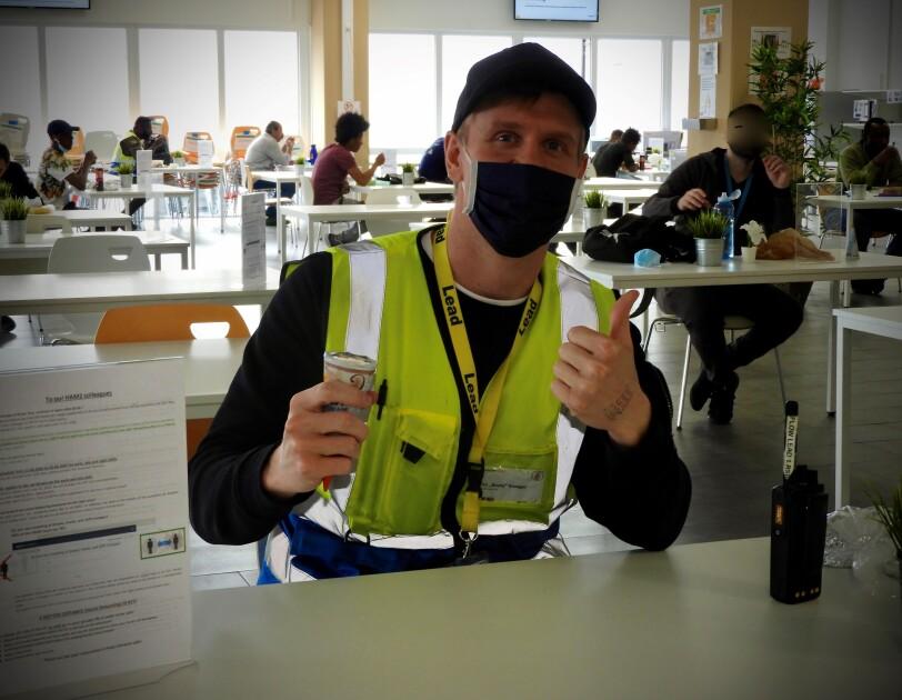 Ein Mitarbeiter mit Mundschutz und gelber Sicherheitsweste am Eisessen.