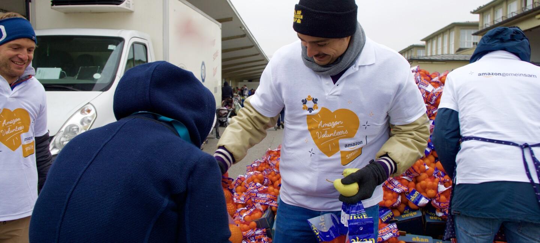 """Ein Freiwilliger von Amazon gibt Obst aus. Er trägt ein weißes Shirt mit Aufdruck """"Amazon Volunteers"""""""