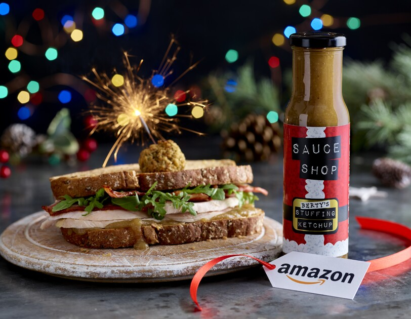 A sandich containing turkey and stuffing balls, next to the stuffing ketchup on a dinner table with an Amazon Label. There is also a sparkler sticking into the sandwich.