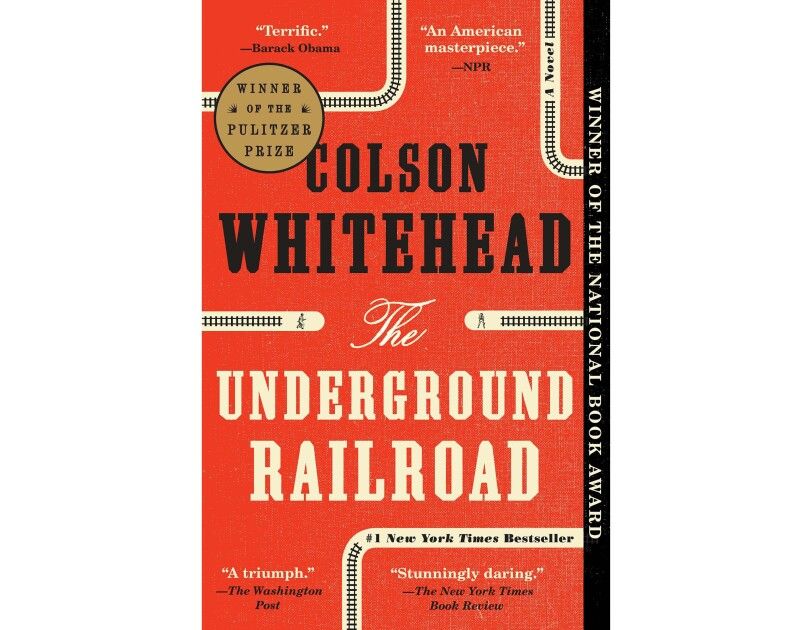 Book cover for The Underground Railroad by Colson Whitehead. The background is red, with small railroad paths in the top, middle and bottom of the page. Author's name is in black all-caps font, the title is in ivory text.