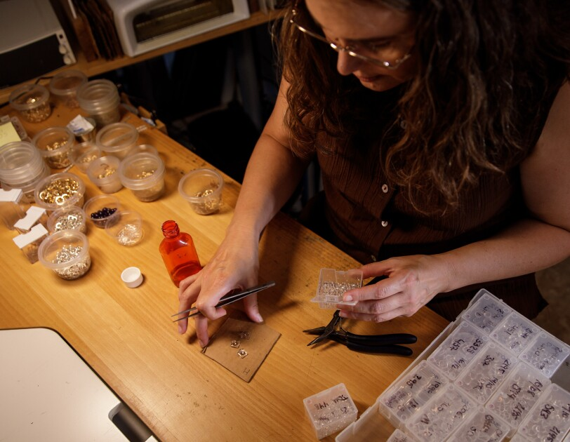 A woman sits at a work table crafting jewelry.