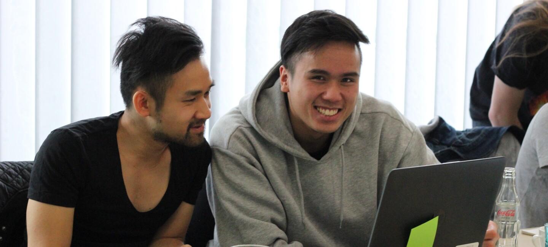 Tuan Hoang mit anderen Teilnehmern lachend beim Workshop