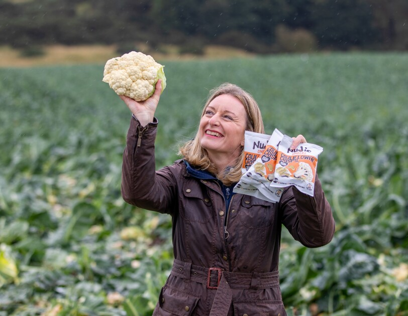 Business owner holding up a cauliflower and nudie snacks