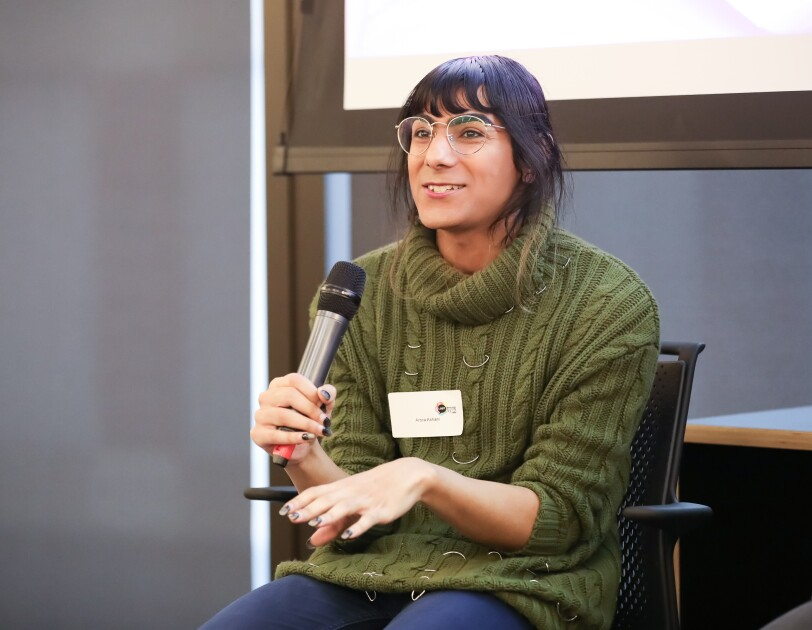 Arora Ashani is a developer for YOOX Net-a-Porter and co-founder of Non-Binary in Tech, holding a mic and giving a talk at the LGBT Leaders in STEM event.