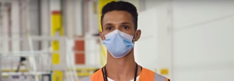 Uomo ripreso a mezzo busto all'interno di un magazzino Amazon. Indossa una mascherina chirurgica sul volto e un giubbino catarinfrangente arancione. Al collo porta appeso un cordino porta-badge nero e una t-shirt bianca.