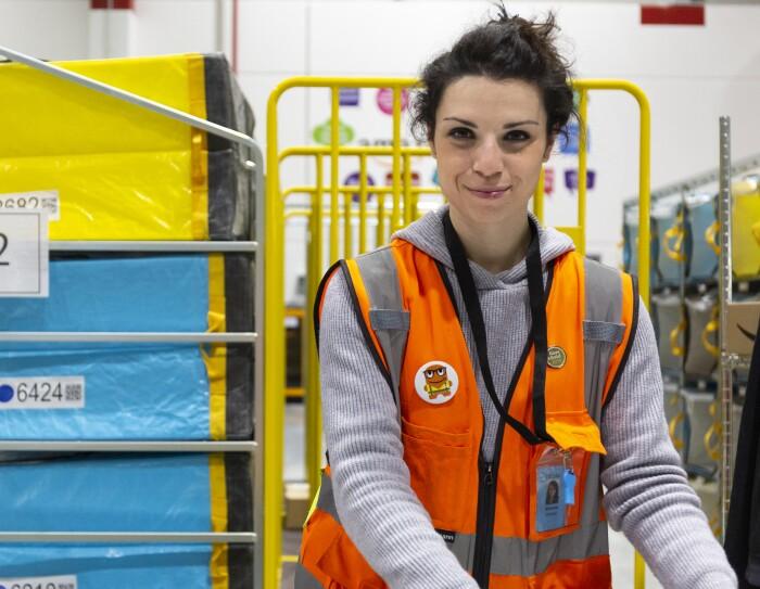 Simona Calzolari, operatrice di magazzino, inquadrata nel deposito di smistamento di Brandizzo. Indossa un giubbotto arancione ed è circondata da carrelli gialli e pacchi celesti e gialli.