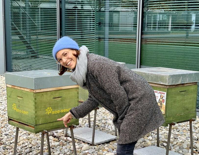 Eine Frau mit blauer Mütze steht an einem grünen Bienenkasten und schaut in die Kamera.