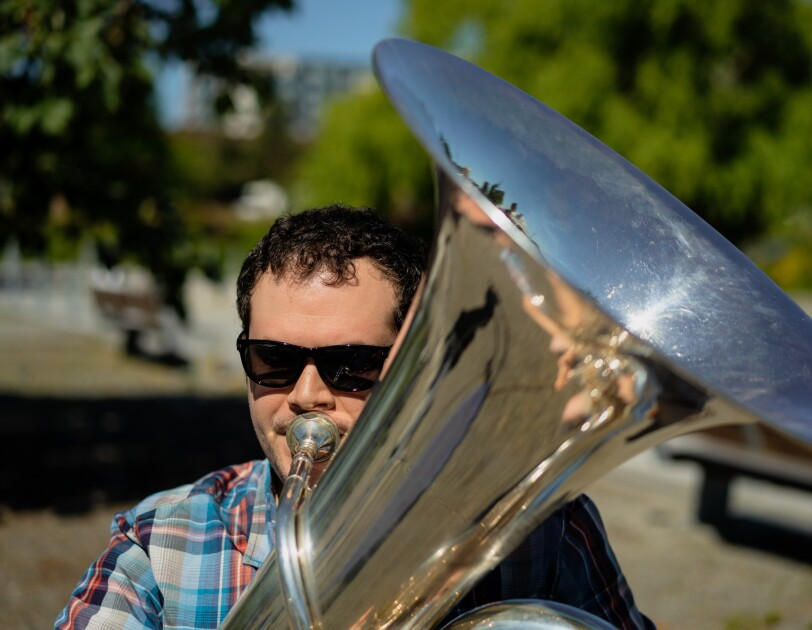 A man in sunglasses plays a tuba outdoors.