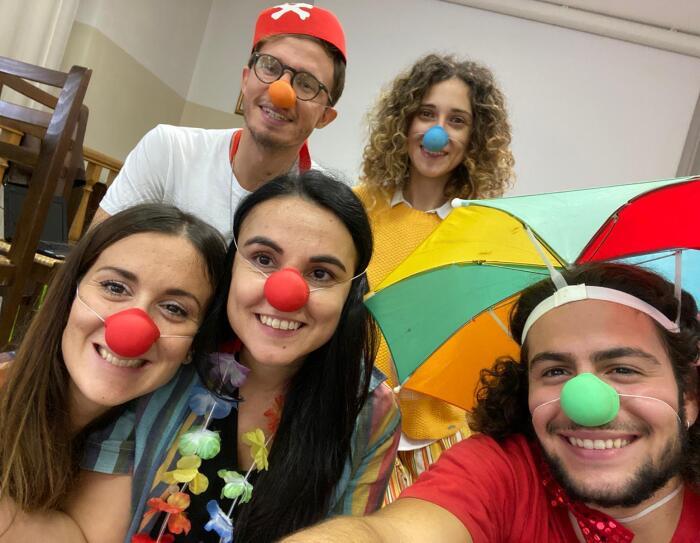 Primo piano dei dipendenti Amazon durante il corso di clownterapia. Indossano nasi di gomma rossi e verdi e sono travestiti da clown.