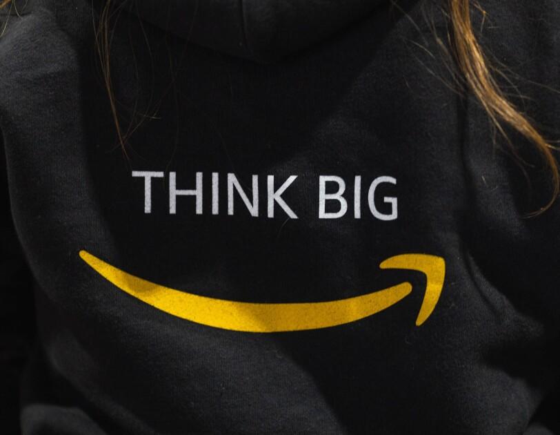 """Napis """"Think Big"""" na czarnej koszuli, pod spodem logo Amazon"""