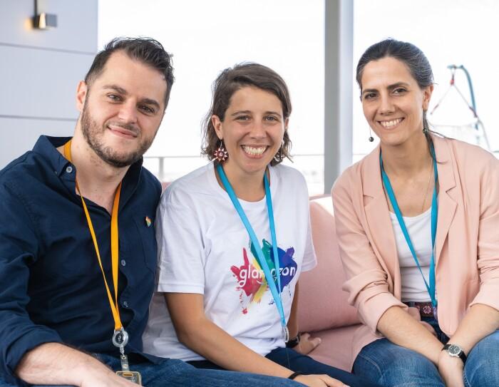 Simone Fortunini, Coia Pons y Eva Ahijado, miembros de glamazon, en las oficinas corporativas de Amazon en Madrid.  Los tres están sentados, miran a cámara y sonríen. Simone viste con una camisa azul, Coia con la camiseta de glamazon y Eva con una camiseta blanca y una americana de color salmón.
