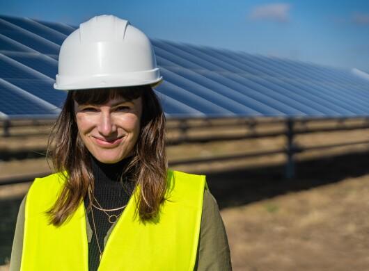 Denise Hugo, jefa de proyectos de Energías Renovables de Amazon. Ella está delante de las placas solares. Va vestida con casco blanco y chaleco amarillo. Tiene el pelo castaño y le llega más allá de los hombros. LLeva tres collares de oro que están por encima de un jersey de cuello alto marrón.