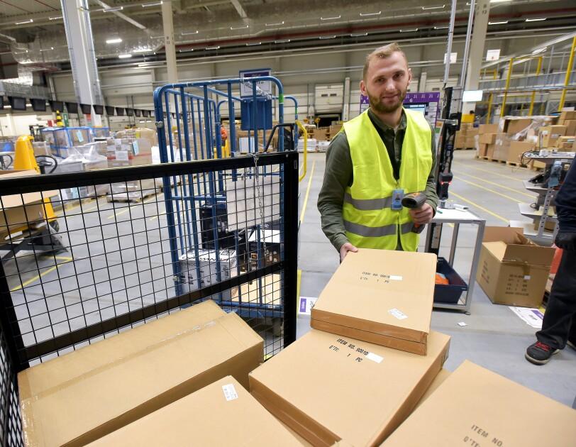 Ein Logistikmitarbeiter mit gelber Sicherheitsweste steht vor einem Packwagen. In der einen Hand hält er einen Karton, in der anderen einen Scanner.