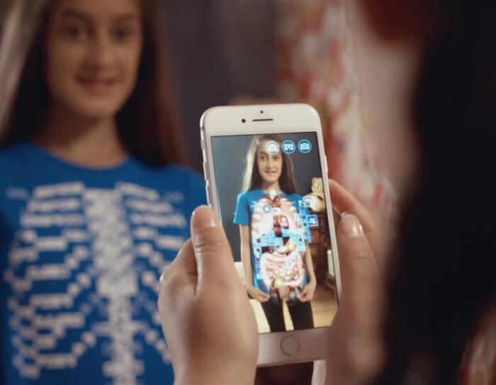 Bambina di spalle inquadra con lo smartphone una bamabina che indossa una t-shirt Curiscope. Sullo schermo dello smartphone si vede la bambina inquadrata con una ricostruzione dei suoi organi interni.