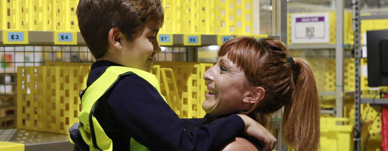Mujer amazonian trabajadora de un centro logístico agarra a un niño de unos diez años. Ella, que sonríe, lleva el pelo recogido y un jersey negro sin mangas. El niño va con chaleco y le sonríe tímidamente.